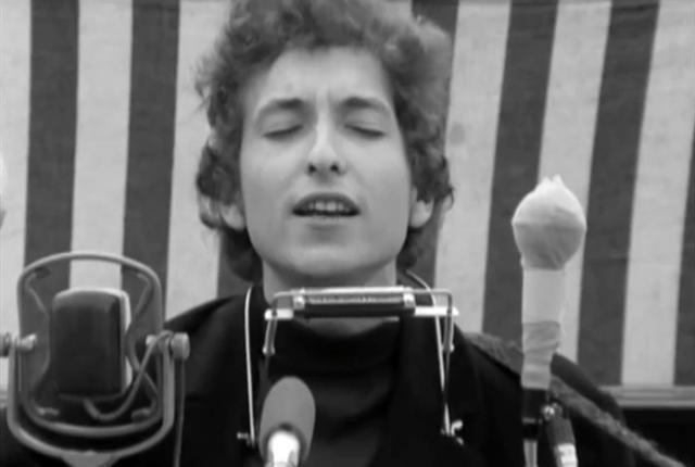 Dylan spiller en tidlig versjon av «Mr. Tambourine Man» i kraftig motvind under Newport Folk Festival, 1964. Kilde: bobdylan.tv.