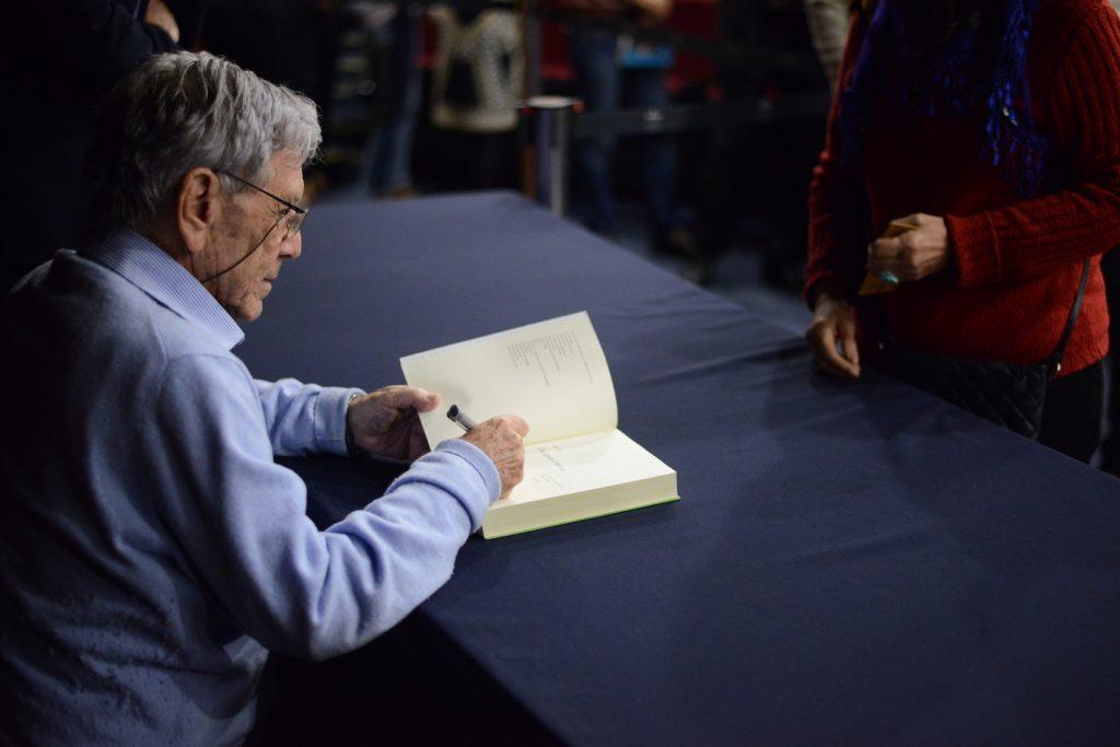 Amos Oz signerer bøker.